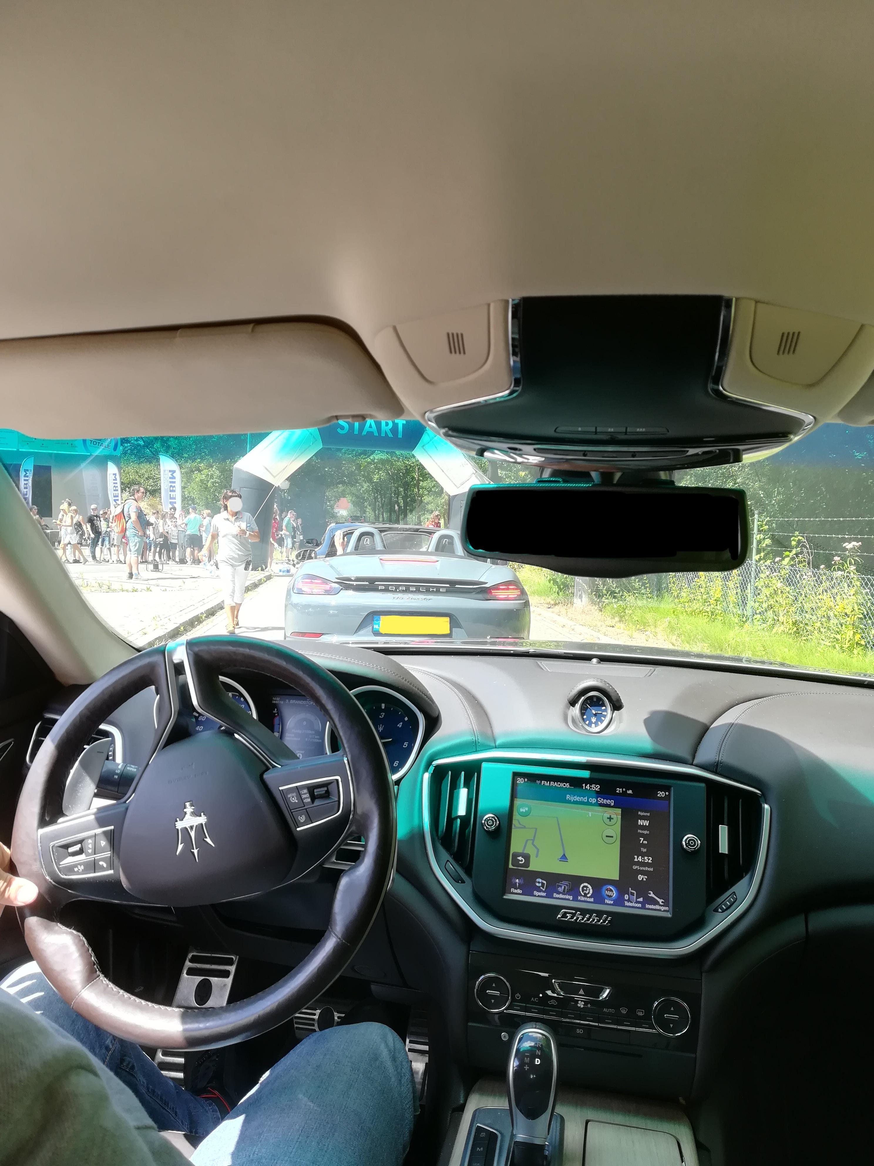 Binnenzijde, dashboard van de Maseratti. Porsche van achteren. Start bij Autotron.